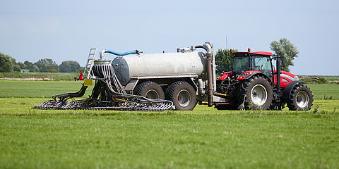 Tractor distributes organic fertilizer on a field